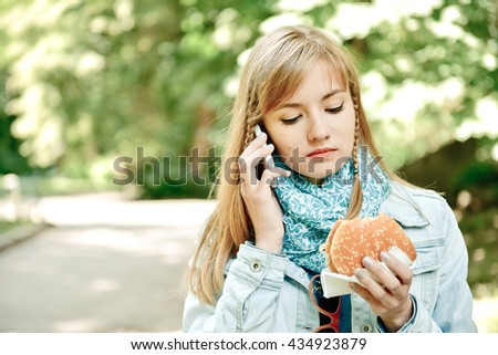 Young woman eating fast food outdoor and talking on telephone gadget. Summer green park city on background