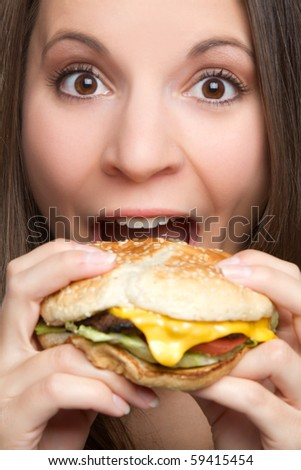 Young woman eating hamburger food - stock photo