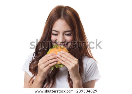 Young woman eating hamburger on white background - stock photo
