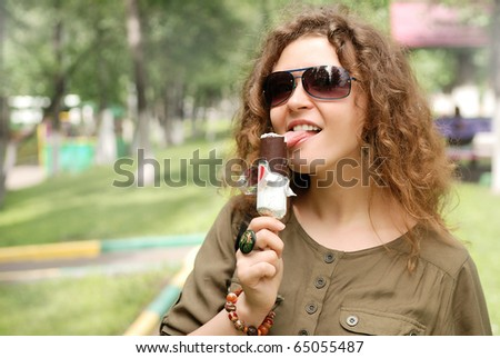 young woman eating ice-cream at street