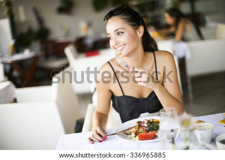 Young woman eating in the restaurant - stock photo