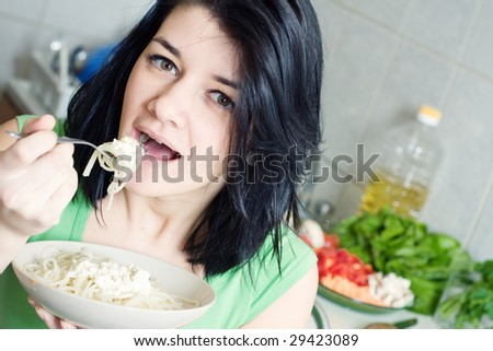 Young woman eating pasta in the kitchen - stock photo