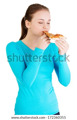 Young woman eating pizza. Isolated on white. - stock photo