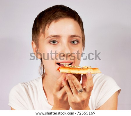 young woman eating pizza on gray background