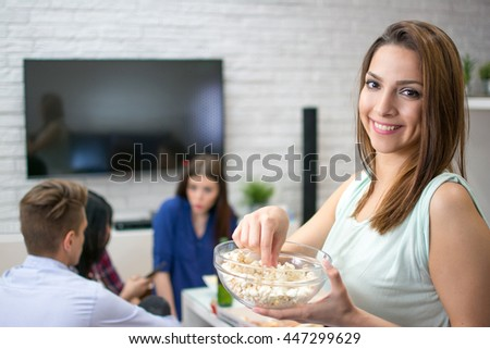 Young woman eating popcorn while sitting with her friends at home. - stock photo