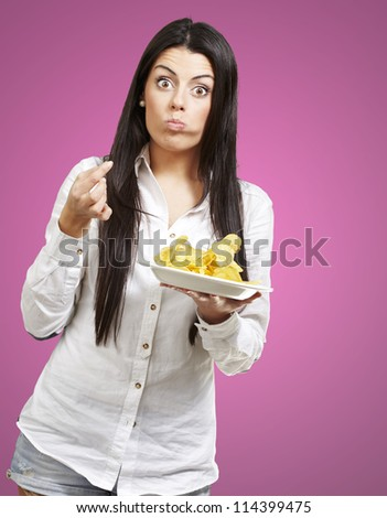 young woman eating potatoe chips against a pink background - stock photo
