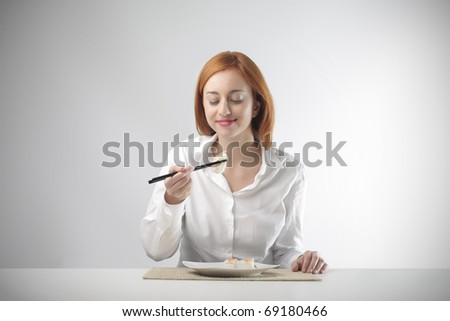 Young woman eating sushi - stock photo