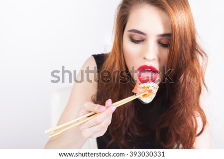 Young woman eating sushi at Japanese restaurant. Asian nutrition. Roll. Fast food delivery. Red fish, rice, soy sauce. Healthy - stock photo