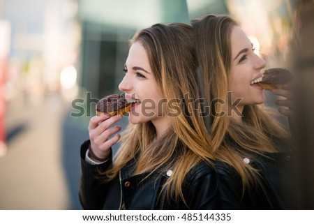 Young woman eating tasty donut outdoor - reflection in shop window