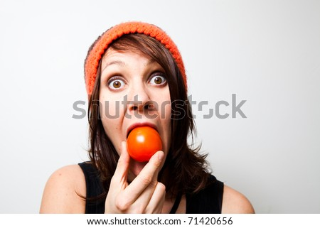 Young woman eating tomato. Funny facial expression.
