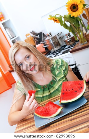 Young woman eating watermelon in the kitchen - stock photo