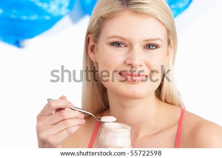 Young Woman Eating Yoghurt In Studio - stock photo