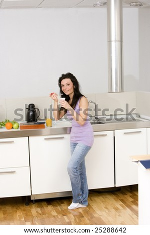 young woman eating yogurt at home in casual wear.Concept of healthy food.