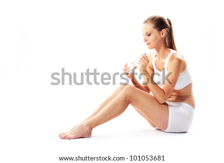 Young woman eating yogurt on white background - stock photo
