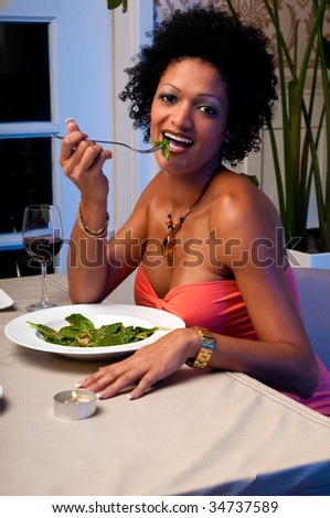 Young woman eats healty salad in a restaurant - stock photo