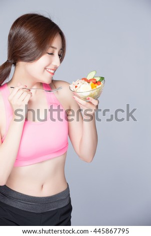 young woman eats salad and smiles isolated on gray background