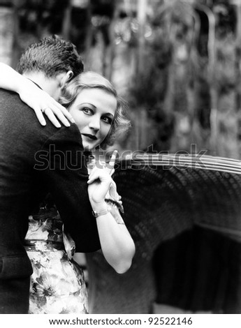 Young woman embracing a man and pointing towards an information board - stock photo