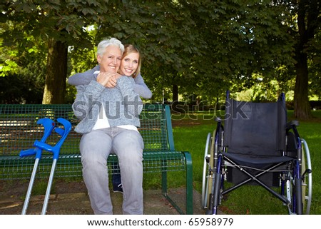 Young woman embracing an elderly handicapped woman on a park bench - stock photo