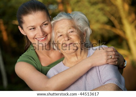 Young woman embracing her grandmother. - stock photo