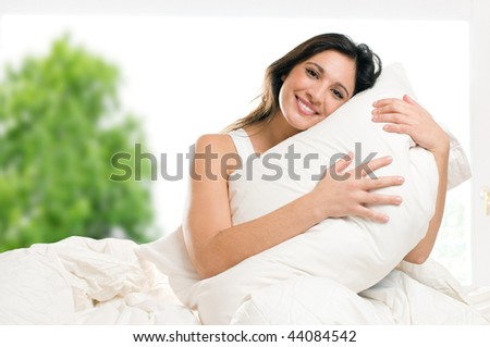 Young woman embracing her pillow in the morning in her bedroom at home