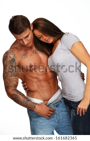 Young woman embracing man with naked muscular torso  - stock photo