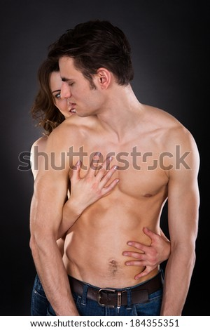 Young woman embracing passionate man isolated over black background - stock photo