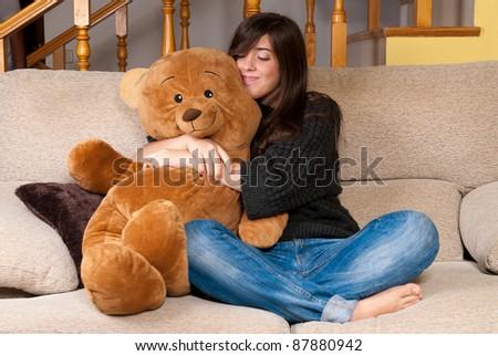 Young woman embracing teddy bear sitting on sofa - stock photo