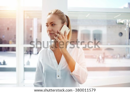 Young woman employee talking on mobile phone with managing director after unsuccessful meeting with clients, confident female having conversation on cell telephone while standing in office interior  - stock photo