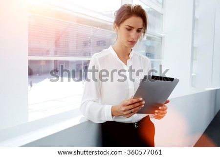 Young woman employee watching video or reading newspaper on digital tablet while standing in modern office interior, intelligent female lawyer using touch pad for explore information about competitors - stock photo