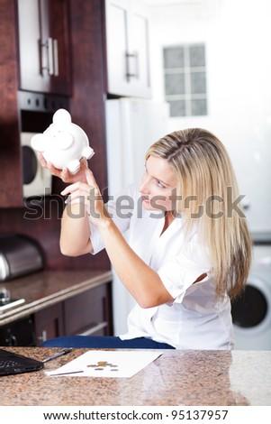 young woman empty piggybank savings to pay bills - stock photo