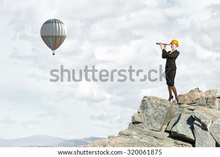 Young woman engineer on rock top looking in spyglass - stock photo
