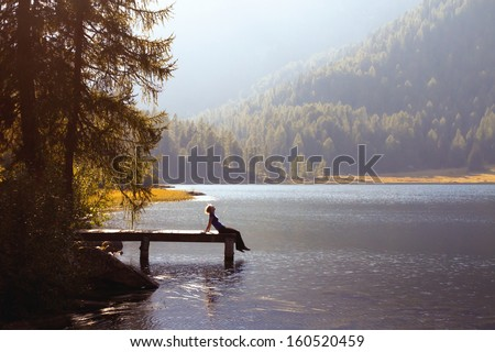 young woman enjoy the nature on the mountain lake - stock photo