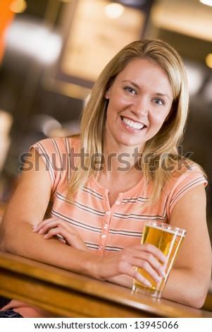 Young woman enjoying a beer at a bar - stock photo