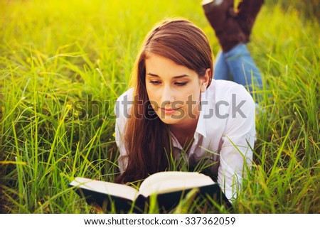 Young Woman Enjoying a Book Reading Outdoors
