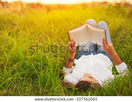 Young Woman Enjoying a Book Reading Outdoors - stock photo