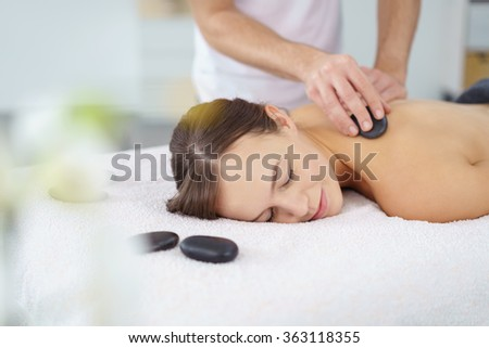 Young woman enjoying a hot rock massage in a spa salon as heated basalt stones are placed on her muscles prior to commencing the massage - stock photo