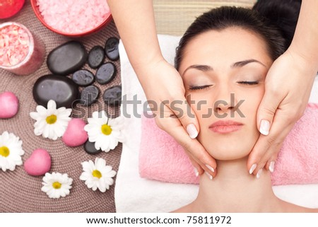 young woman enjoying a massage of the head - stock photo