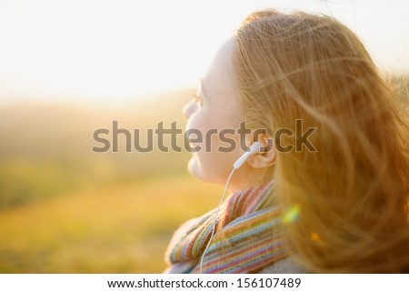 Young woman enjoying a music in the fall season. Autumn outdoor portrait.