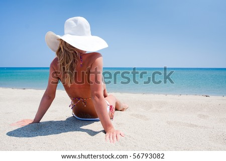 Young woman enjoying a sea view sitting on sand - stock photo