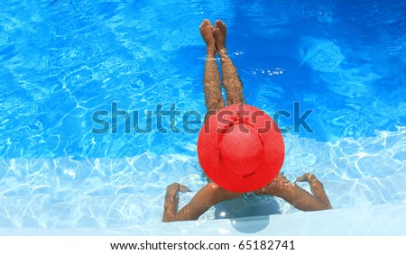Young woman enjoying a swimming pool - stock photo
