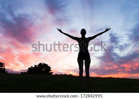 Young woman enjoying beautiful sunset. - stock photo