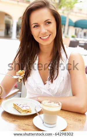 Young Woman Enjoying Coffee And Cake In Cafe - stock photo