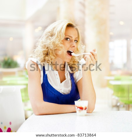 Young woman enjoying coffee time at mall cafe. Eating ice cream dessert - stock photo