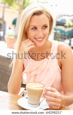 Young Woman Enjoying Cup Of Coffee In Cafe - stock photo
