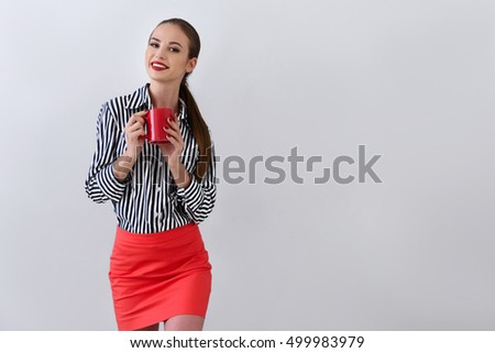 Young woman enjoying cup of coffee in studio