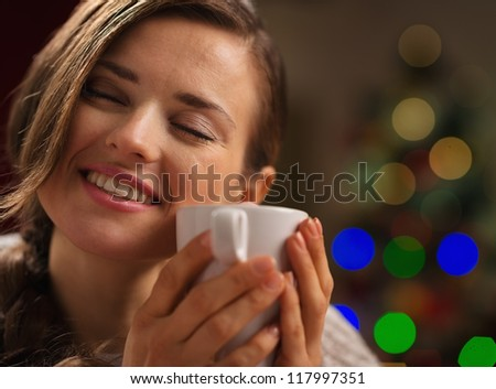 Young woman enjoying cup of hot beverage in front of Christmas lights