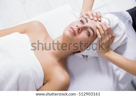 Young woman enjoying facial massage at spa salon.