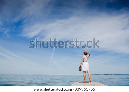 Young woman enjoying freedom at the beach - stock photo