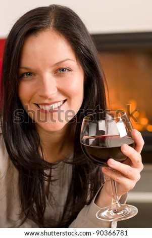 Young woman enjoying glass of red wine by home fireplace - stock photo