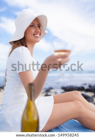 Young woman enjoying glass of wine on the beach - stock photo
